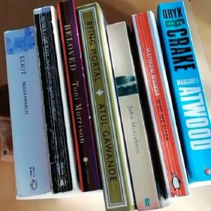 A stack of seven books on a sunlit table