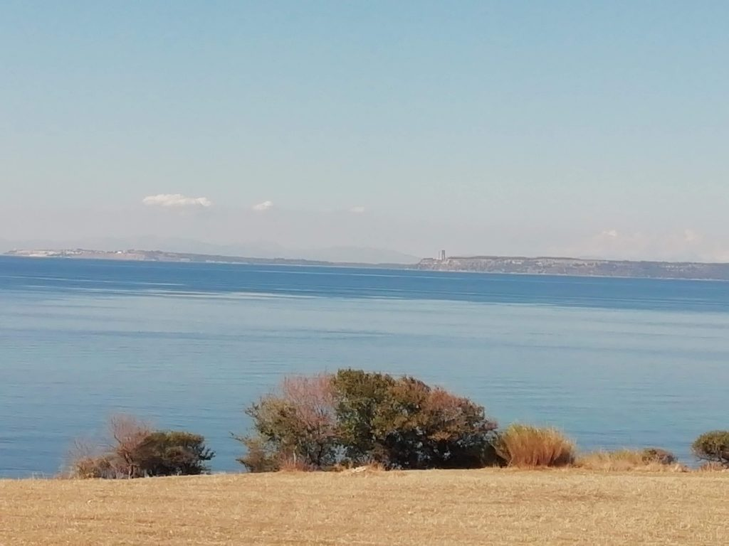 A view across the Dardanelles to the Turkish Abide monument and Seddulbahir at the end of the Gallipoli Peninsula with a foreground of yellow wheat stubble