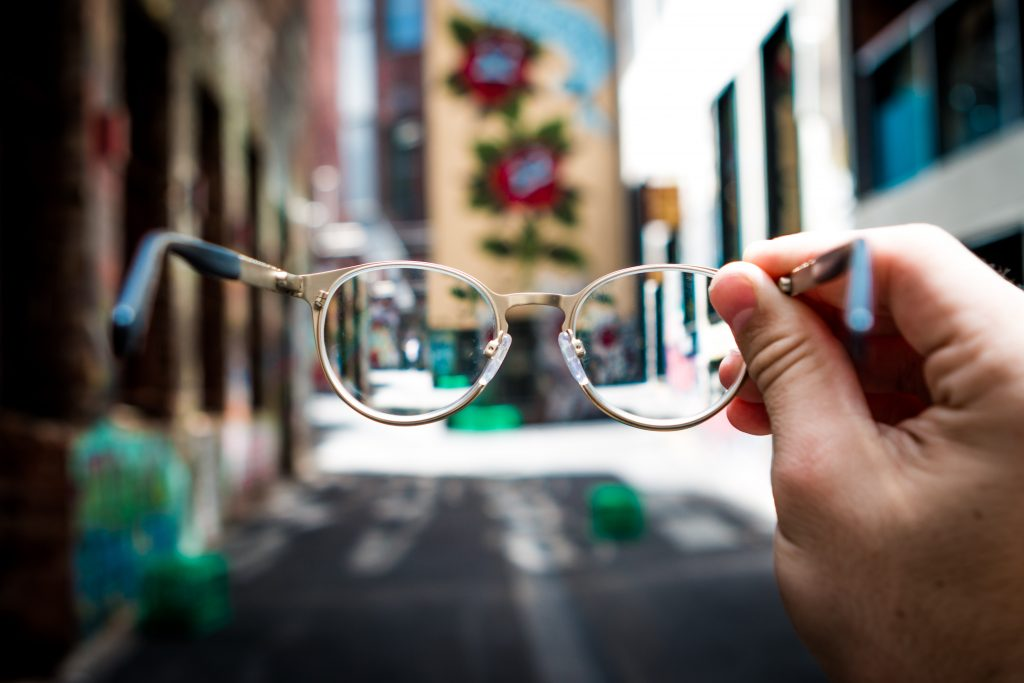 A hand holds a pair of glasses up in the middle of a street, with the image more in focus through the glasses but blurred everywhere else